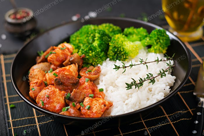 Pieces of chicken fillet with mushrooms stewed in tomato sauce with boiled broccoli