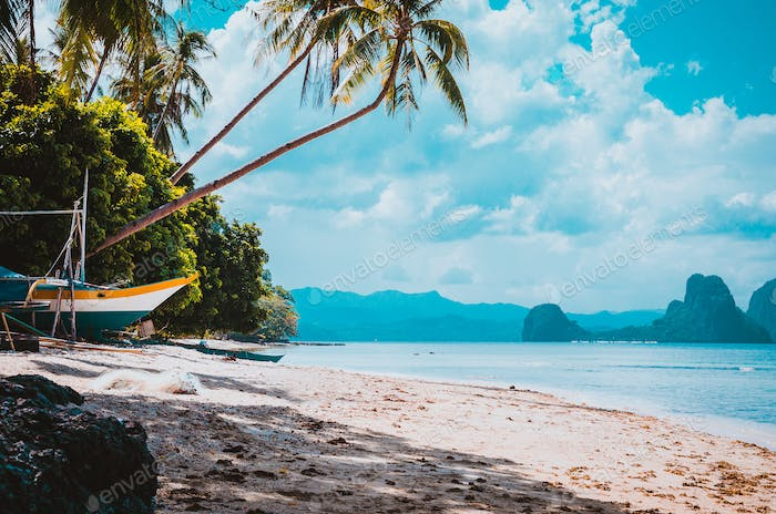 Banca boat on shore under palm trees.Tropical island scenic landscape. El-Nido, Palawan