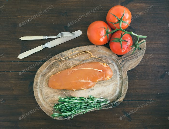 Chicken carpaccio, tomatoes and rosemary on a rustic wooden boar