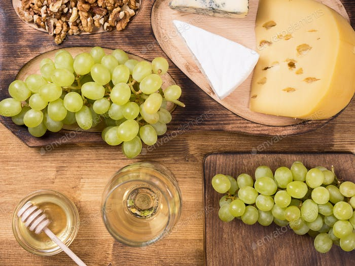 Top view of fresh grapes next to various cheeses on a wooden table
