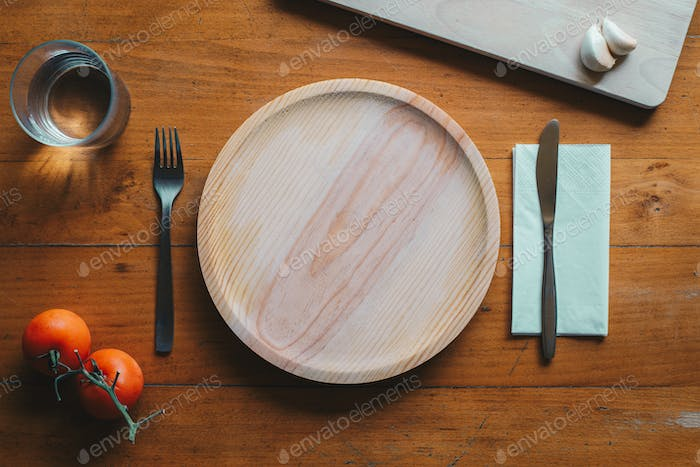 Wooden plate and cutlery against a wood background with mediterranean elements