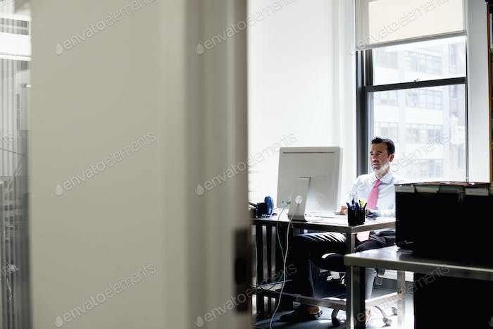 A man seated in an office using a computer.