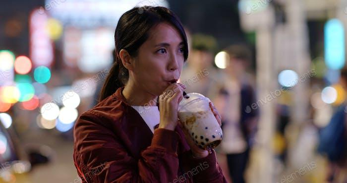 Woman drink of Taiwan iced bubble tea in the night market