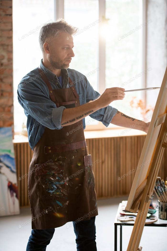 Serious man with paintbrush looking at picture on easel while painting