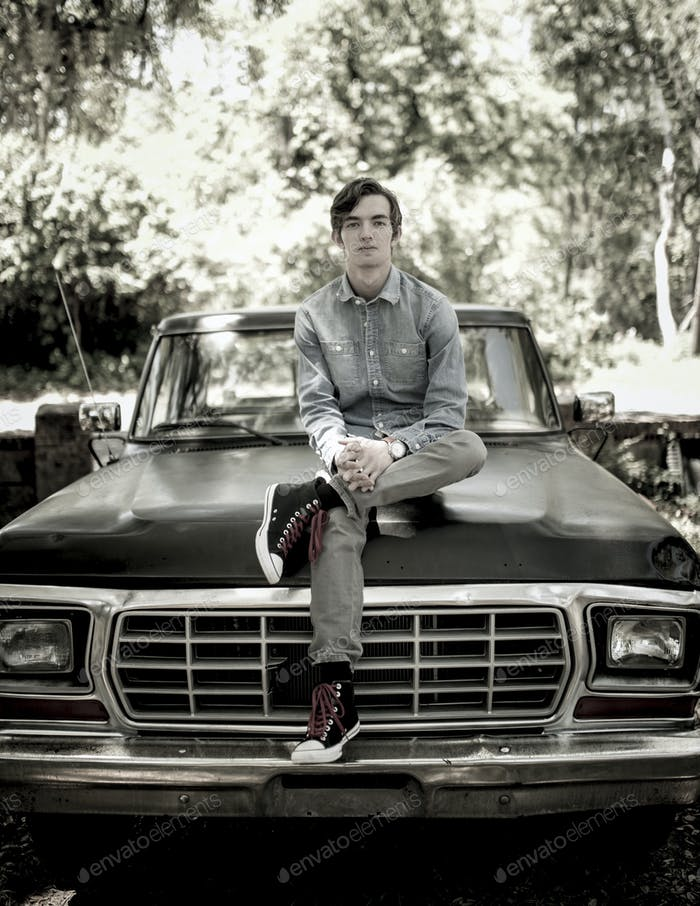 Portrait of young man sitting on old pickup truck