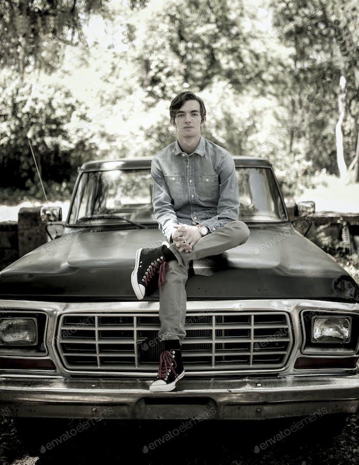 Porträt des jungen Mannes sitzt auf alten Pickup LKW