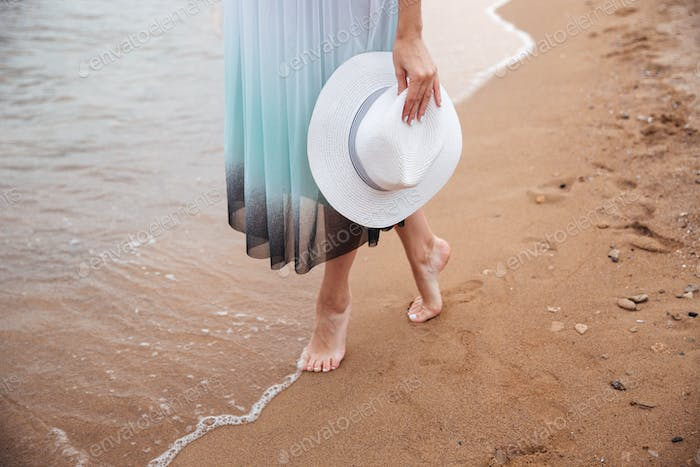 Legs of young woman walking barefoot on the beach