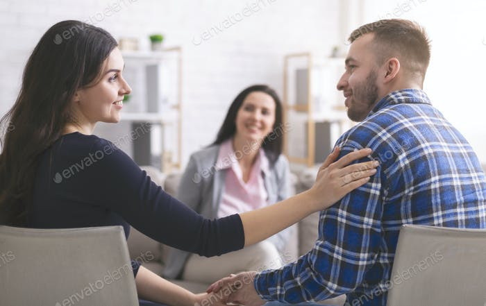 Smiling psychologist looking at happy couple after effective marital therapy