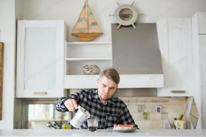 Food, morning and people concept - Handsome man drinking coffee in the kitchen