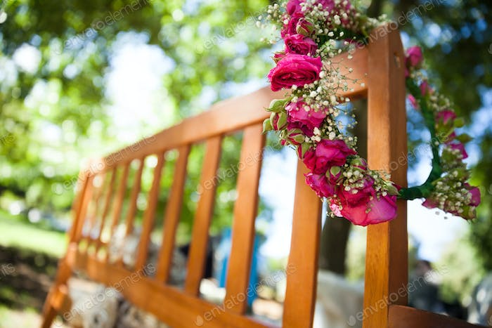 Close-up of  flower wreath on a wooden bench at the park