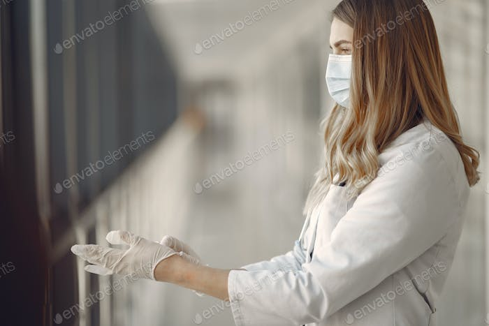 Woman in a mask and uniform puts on gloves