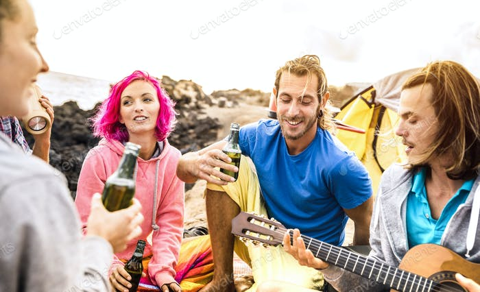 Hipster friends having fun together at beach camping party