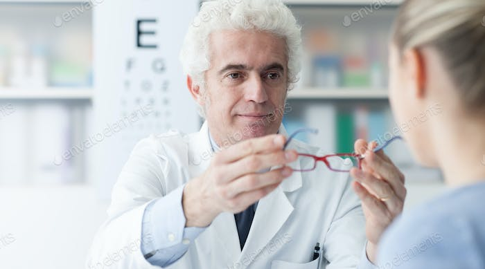 Optician giving glasses to the patient