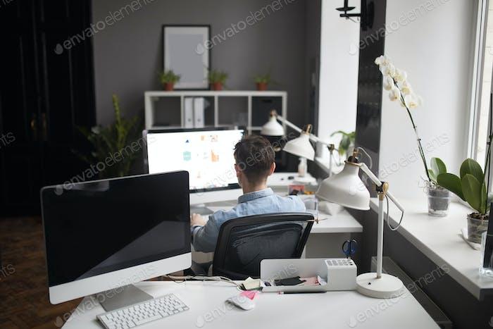 Junge intelligente bärtige Mann arbeitet bei modernen loft studio-offi