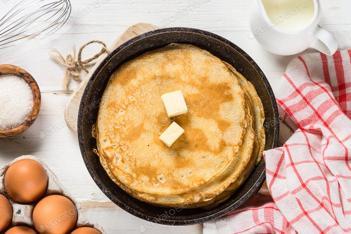 Crepes or thin pancakes in the frying pan with ingredients for cooking