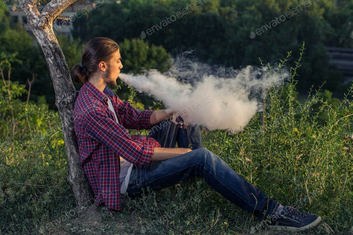 Handsome young man smoking electronic cigarette.