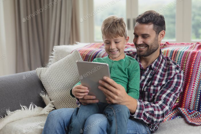 Front view of Caucasian father and son using digital tablet on sofa in a comfortable home