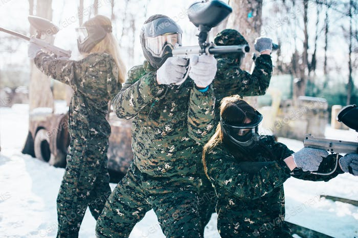 Paintball players in uniform and masks poses