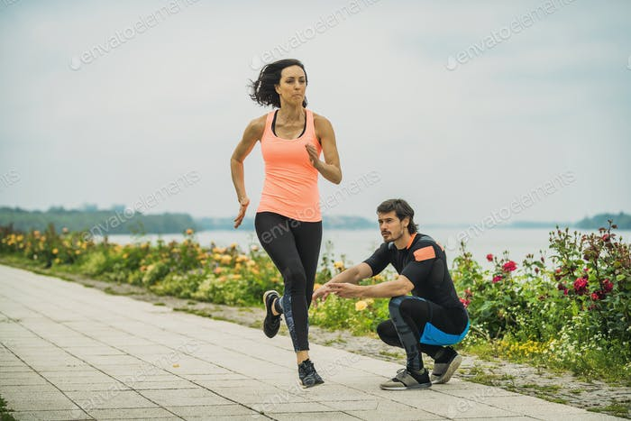 Female Exercising by the River with Personal Fitness Trainer