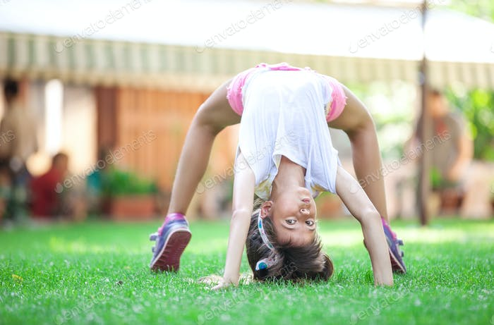 Young girl doing bridge exercise outdoors