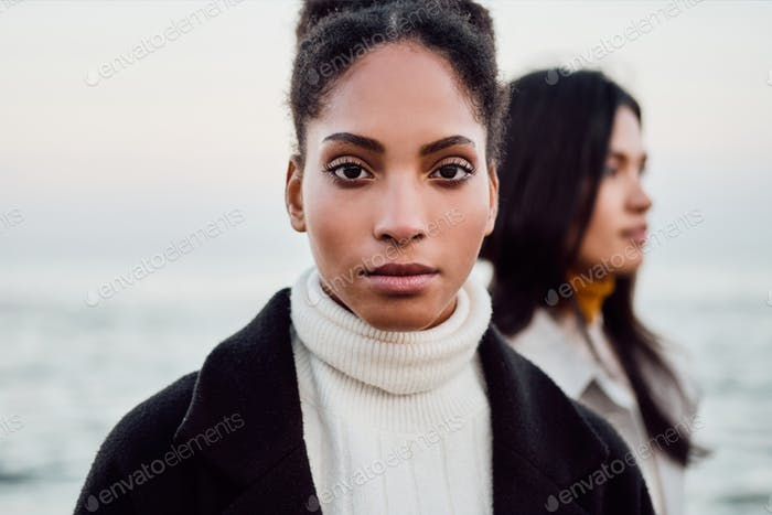 Beautiful casual African American girl intently looking in camera walking with friend by the sea