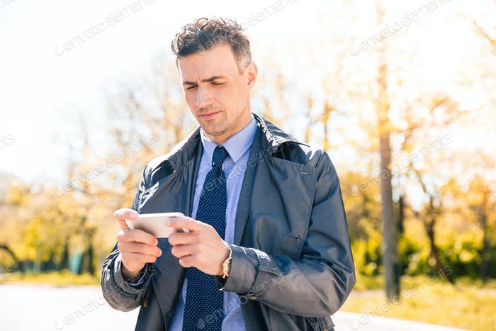 Confident businessman using smartphone