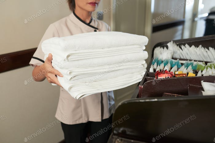 Crop chambermaid with pile of fresh towels