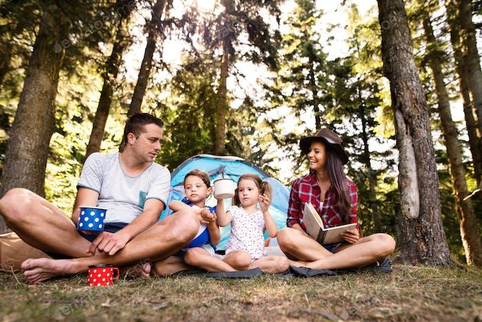 Schöne junge Familie mit Töchtern Camping im Wald.