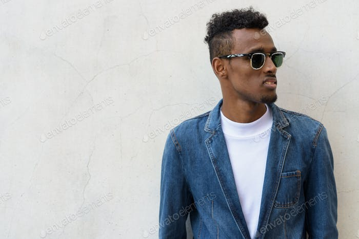 Young bearded African man wearing denim jacket and sunglasses ag