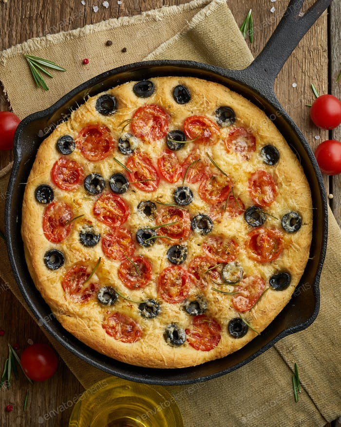 Focaccia, pizza in skillet, italian flat bread with tomatoes, olives and rosemary. Wooden table