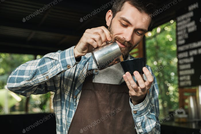 Image of handsome barista man making coffee while working in caf
