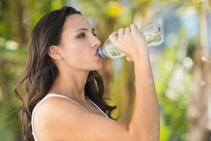 Pretty brunette drinking bottle of water on a sunny day