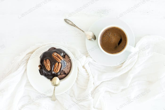 Tasty homemade brown muffin with chocolate ganache icing and pecan nuts, cup of black coffee.