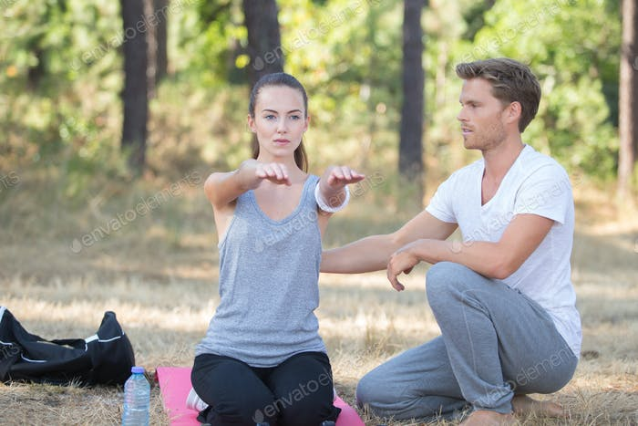 sporty woman exercising with fitness trainer outdoor in forest