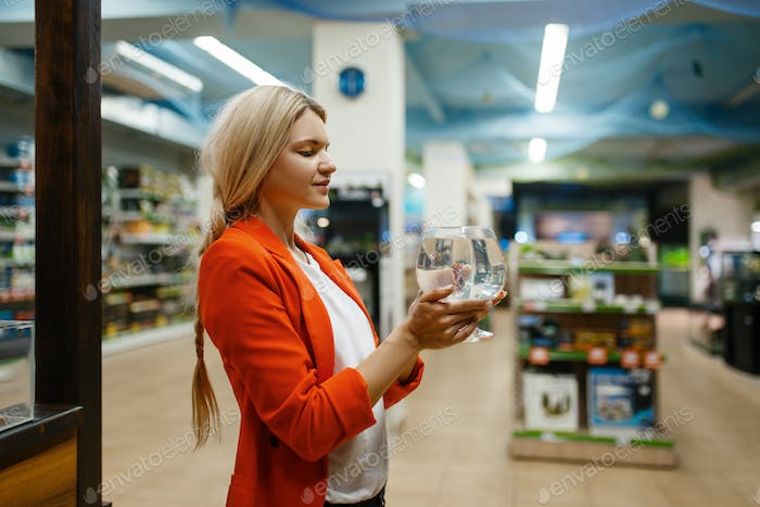 Young woman holds glass with fish, pet store