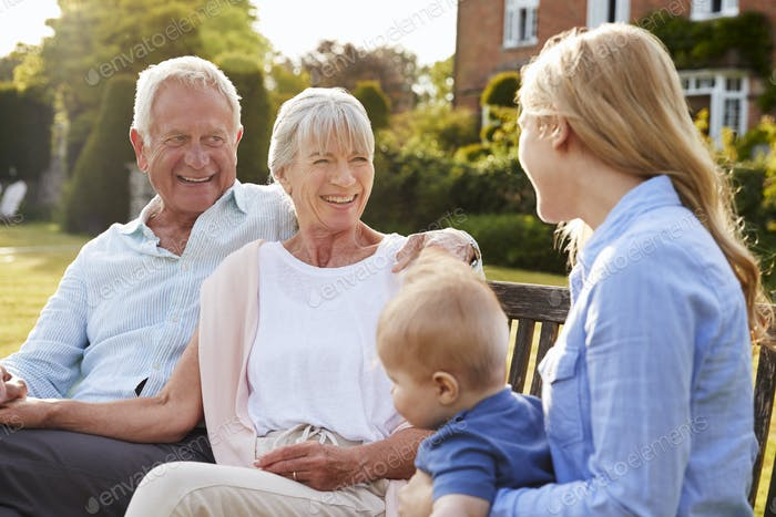 Grandparents Sit Outdoors With Baby Grandson And Adult Daughter