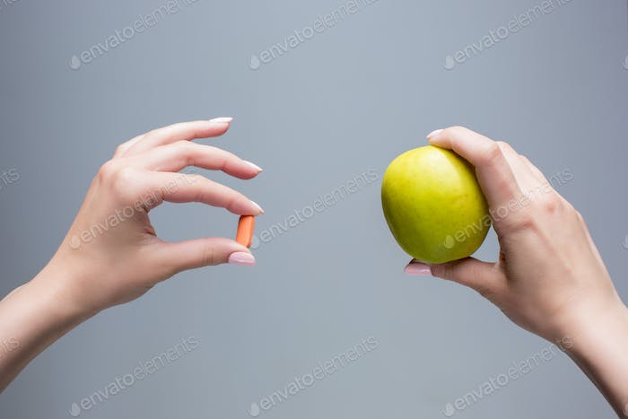 The female hands with apple and pills