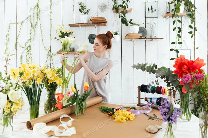 Conentrated young woman collecting colorful bouquet in workshop