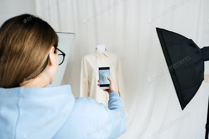 AR VR Technology in Fashion Industry. Female designer shotting clothes on mannequin by cell phone