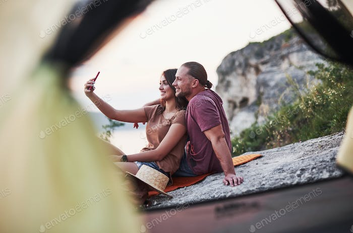 Two person sitting on the rock and watching gorgeous nature
