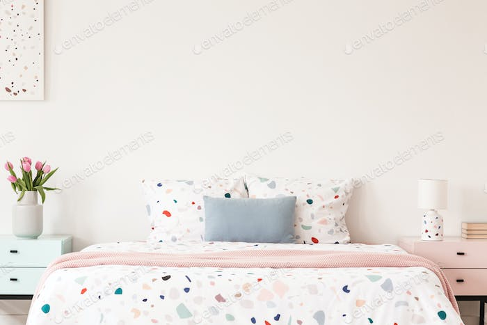 Real photo of a double bed with dotted sheets and pillows on an