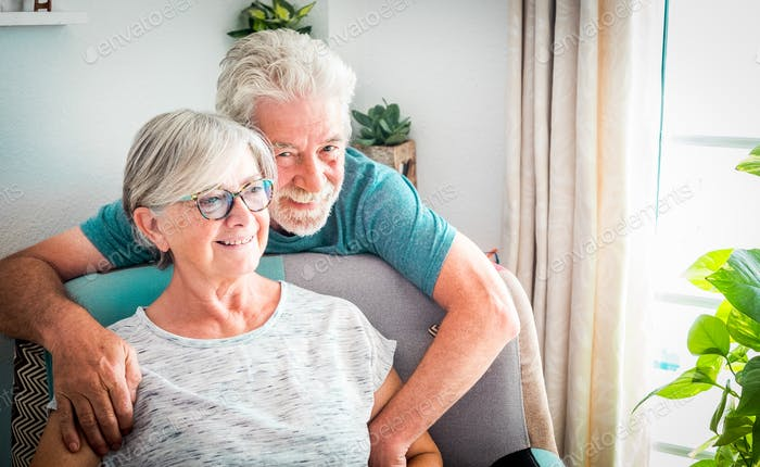 Happy senior couple relax at home on the armchair respecting the quarantine for Covid-19
