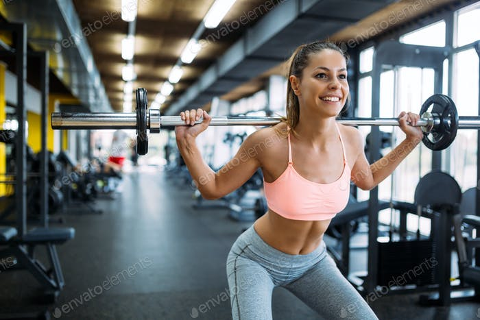 Beautiful active woman doing squats in gym