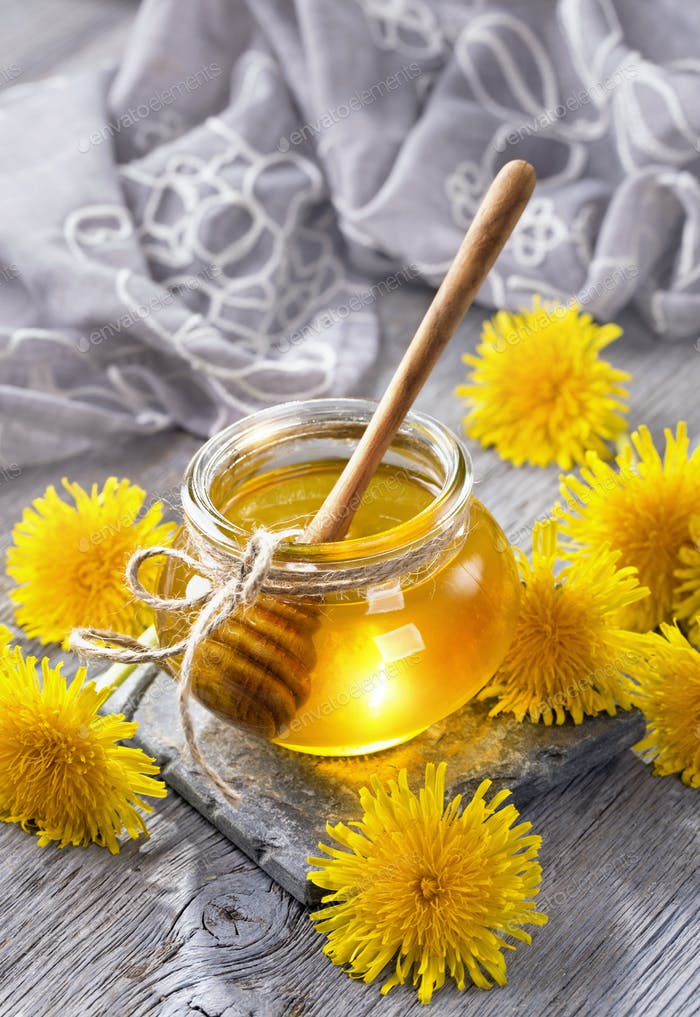 Dandelion honey in a jar and fresh flowers