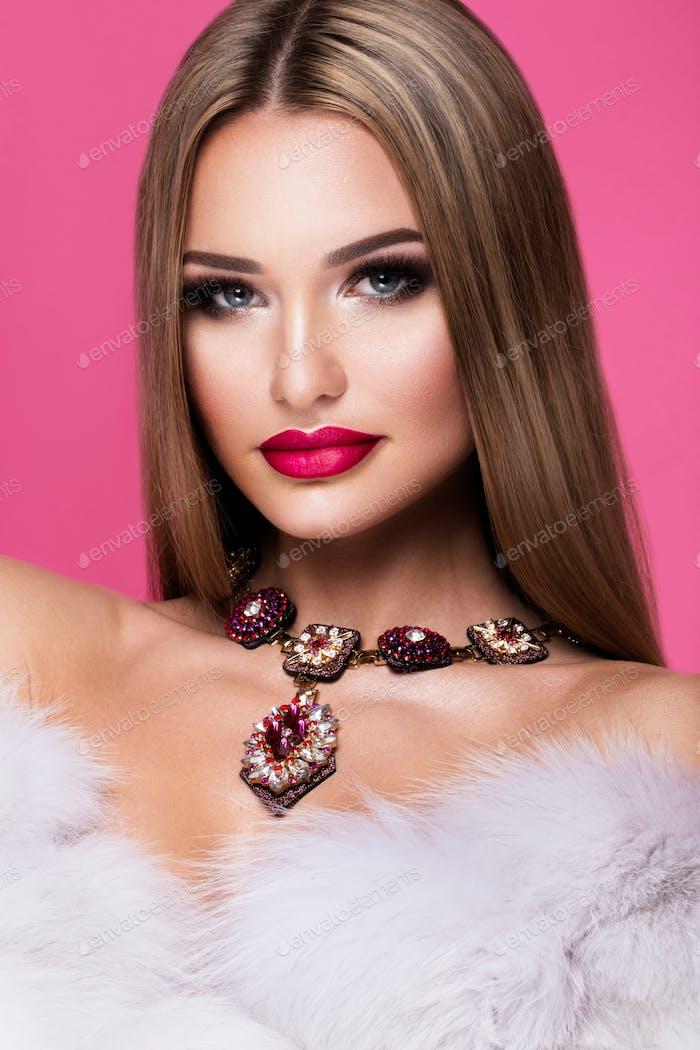 Schöne junge Frau mit langen Haaren posiert auf rosa glänzenden Hintergrund.