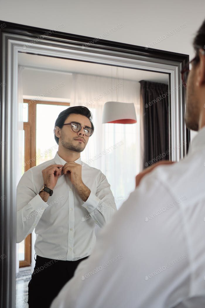 Young handsome man in white shirt, black trousers and eyeglasses thoughtfully looking in mirror