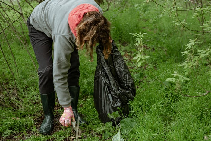 Close-up of a volunteer cleans the forest from debris.