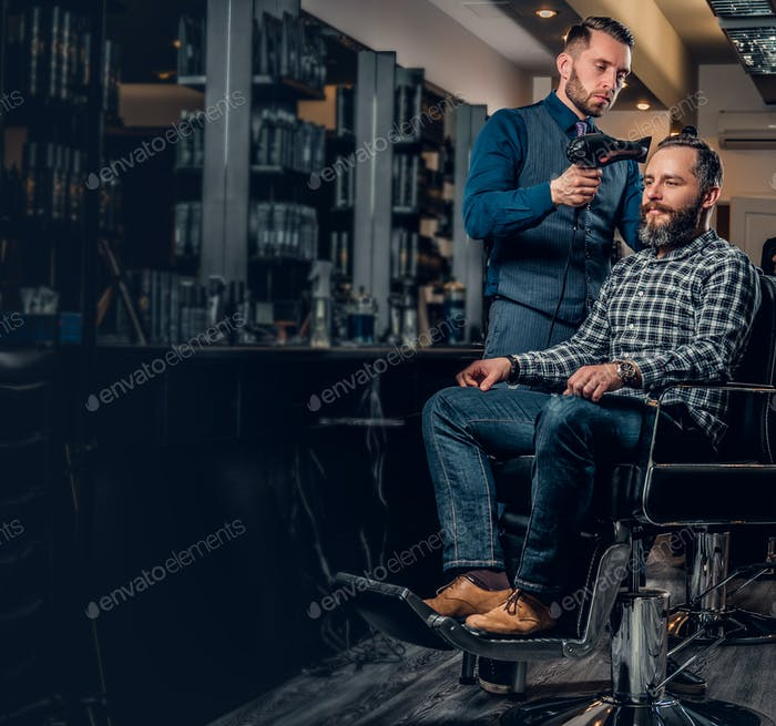 Hairdresser drying man's hair with hairdryer in a saloon.