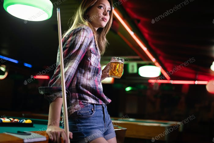 Young beautiful girl is playing billiards. Pleasant pastime, rest, entertainment