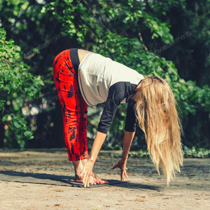 Attractive blond woman doing yoga outdoors